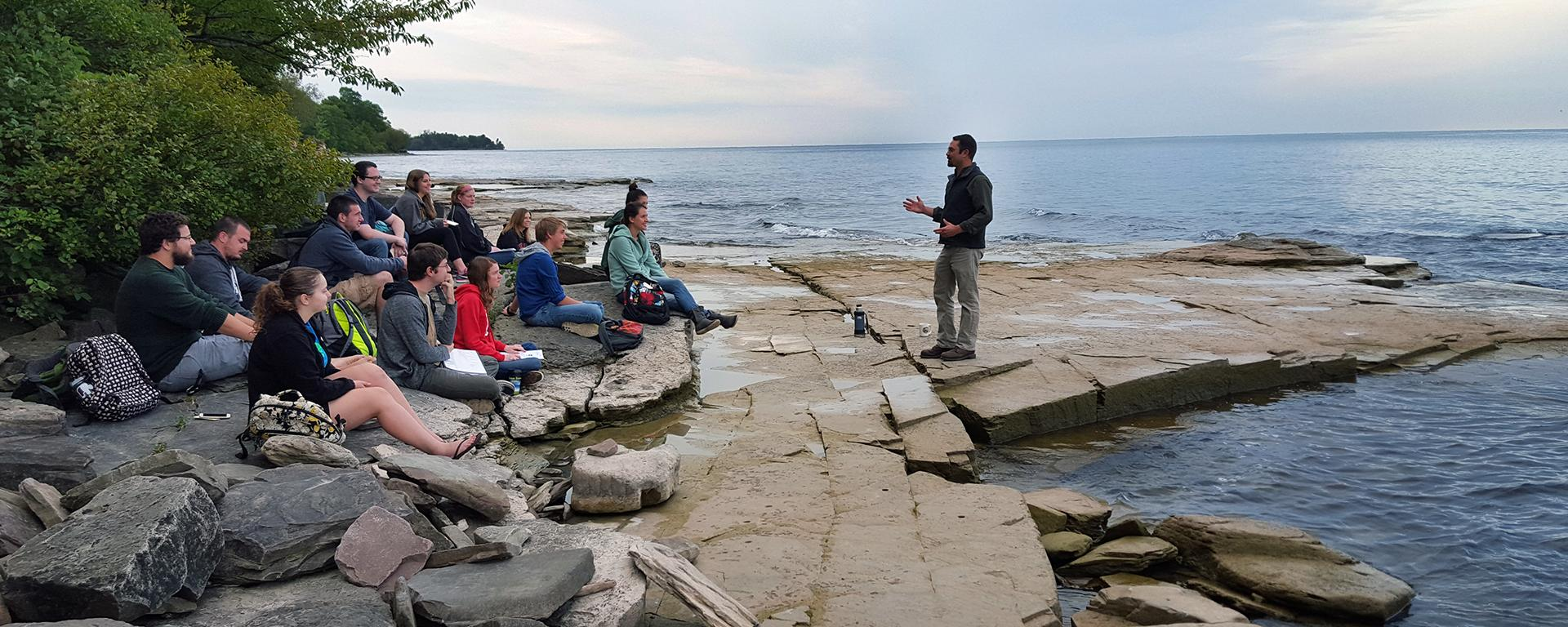 Professor and students near Lake Ontario