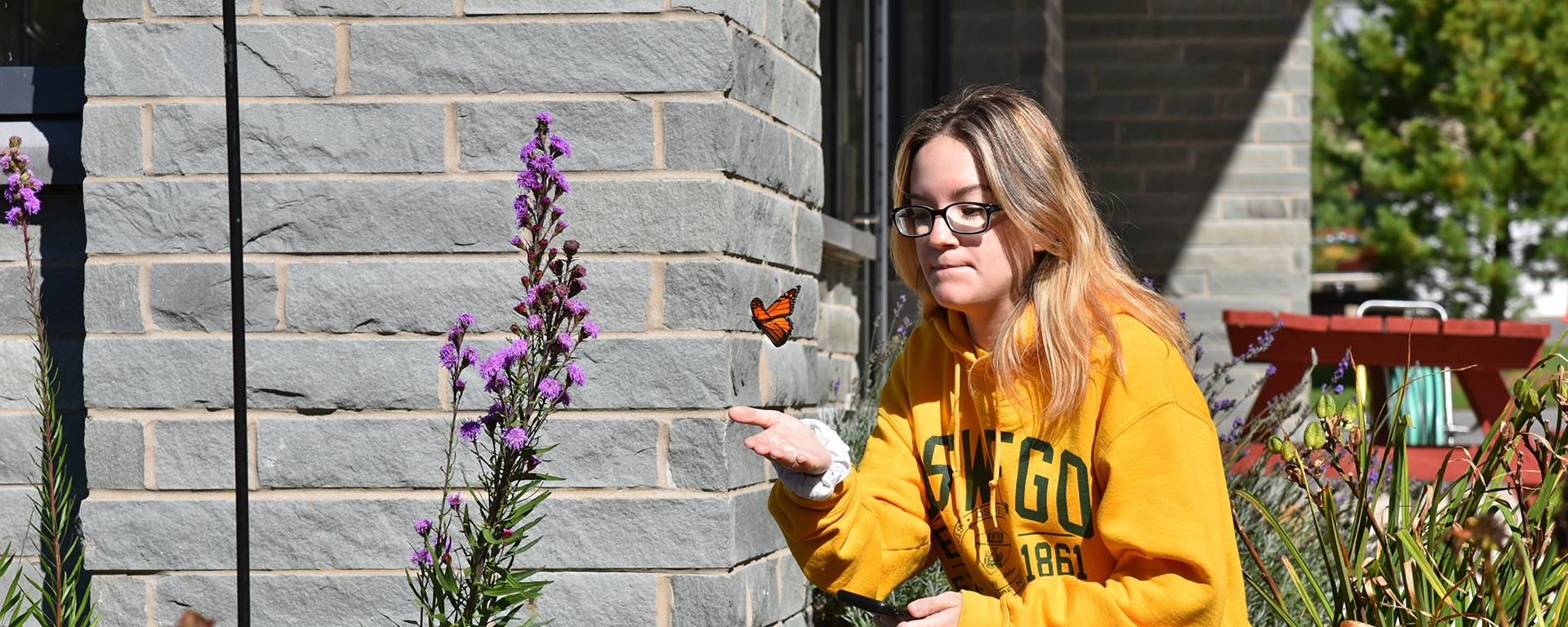 Elena Jones watches a butterfly flying close by
