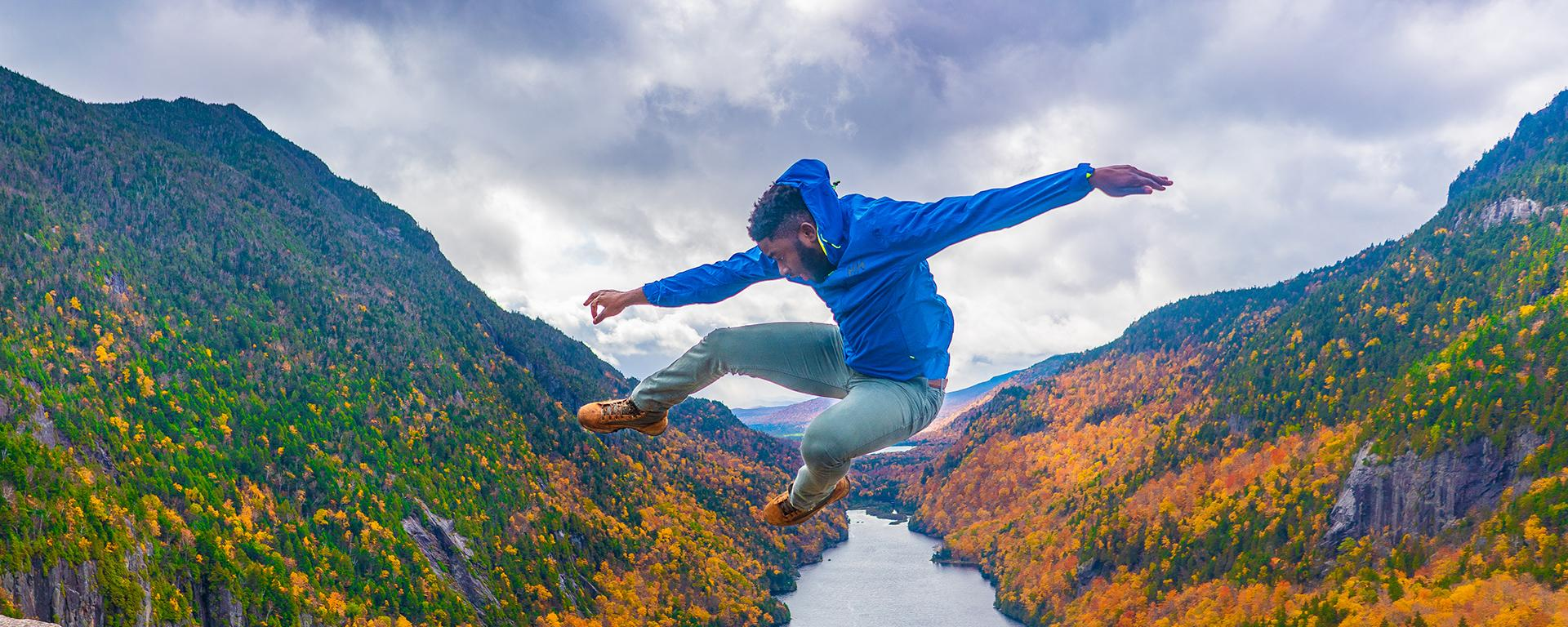 Mic-Anthony Hay jumps in front of fall foliage in the Adirondacks
