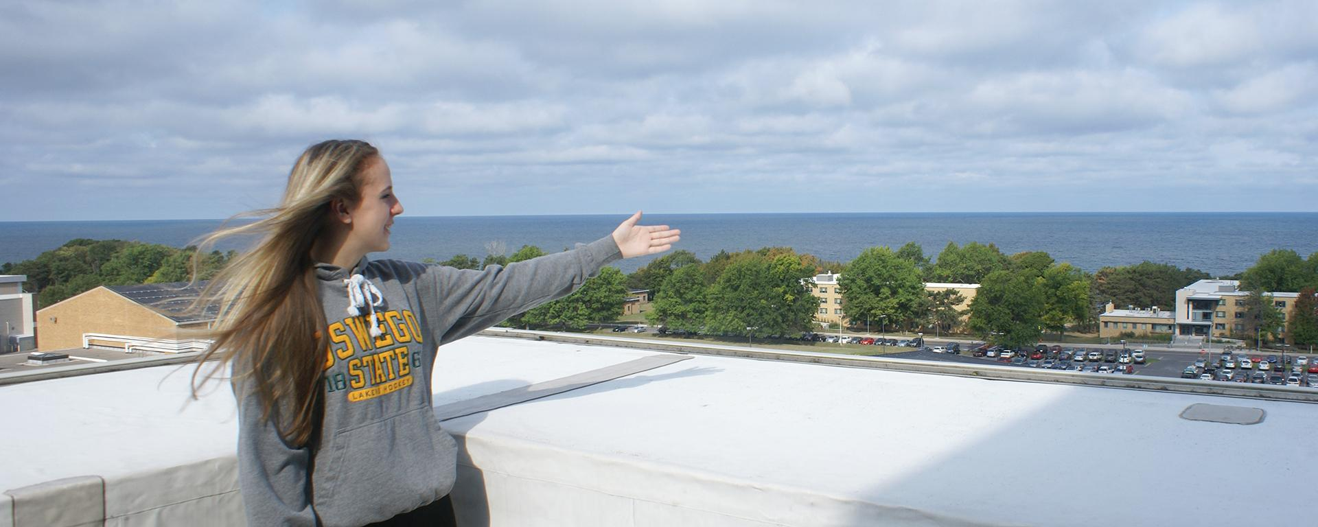 Student tour guide gestures toward campus