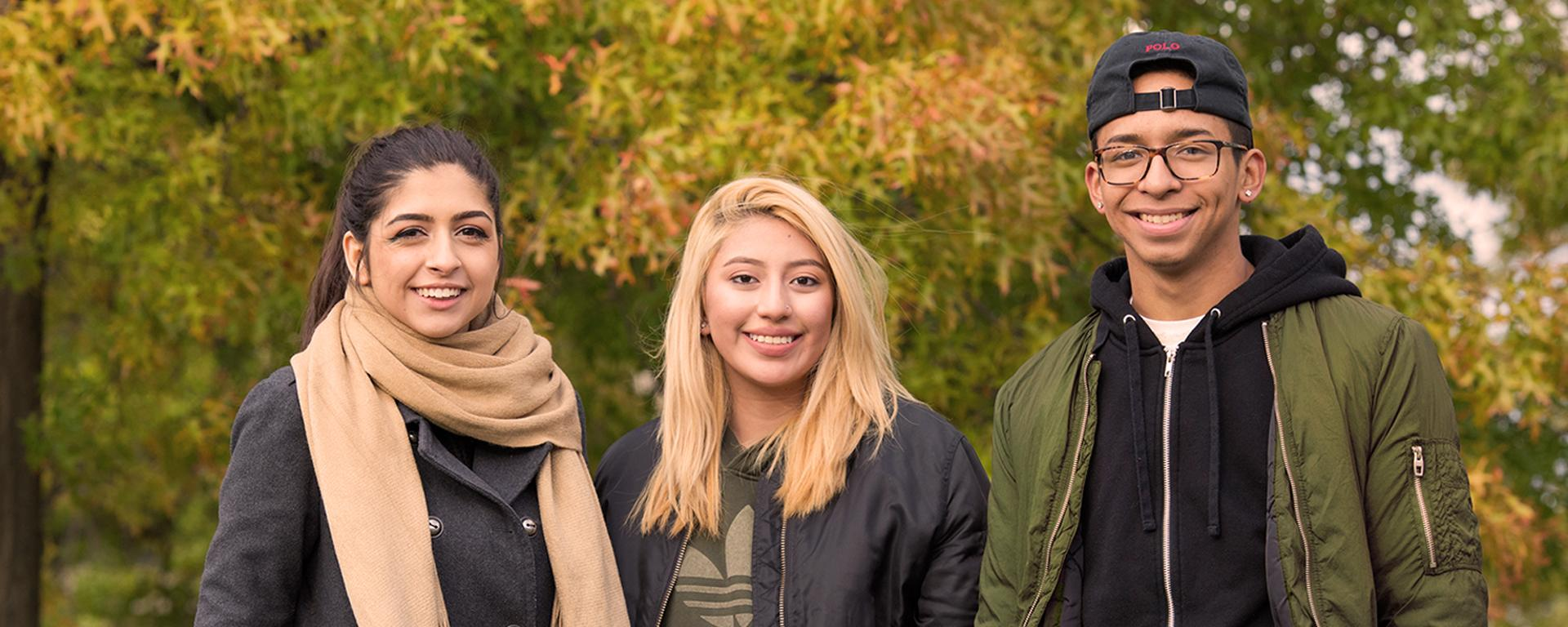 Three students with an autumnal campus background