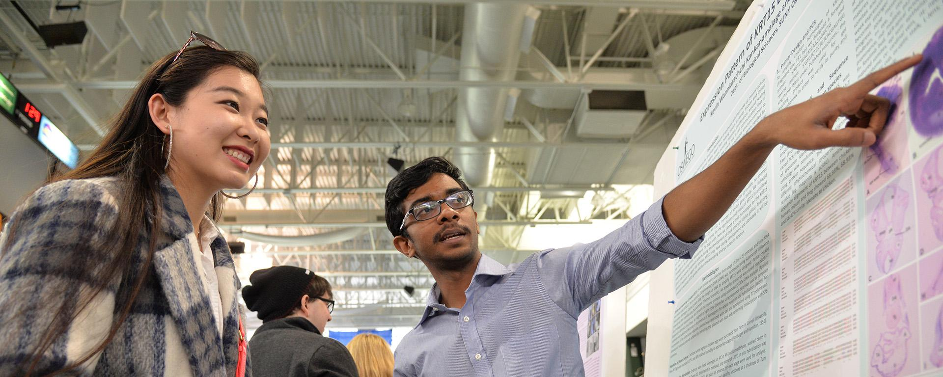 Poster presenter explains his research to student at Quest poster presentation