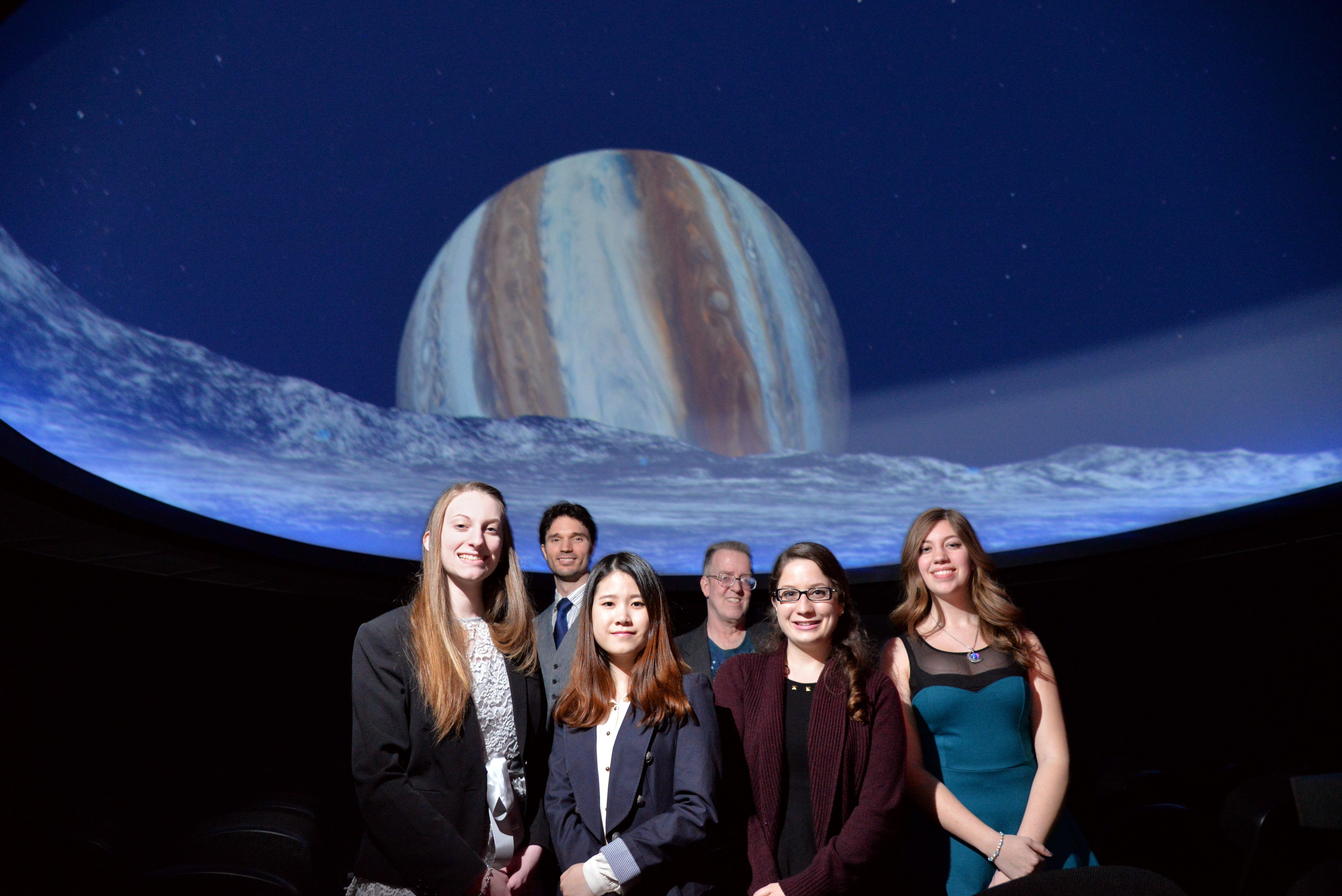 Group of students posing in the planetarium with Professor Roby