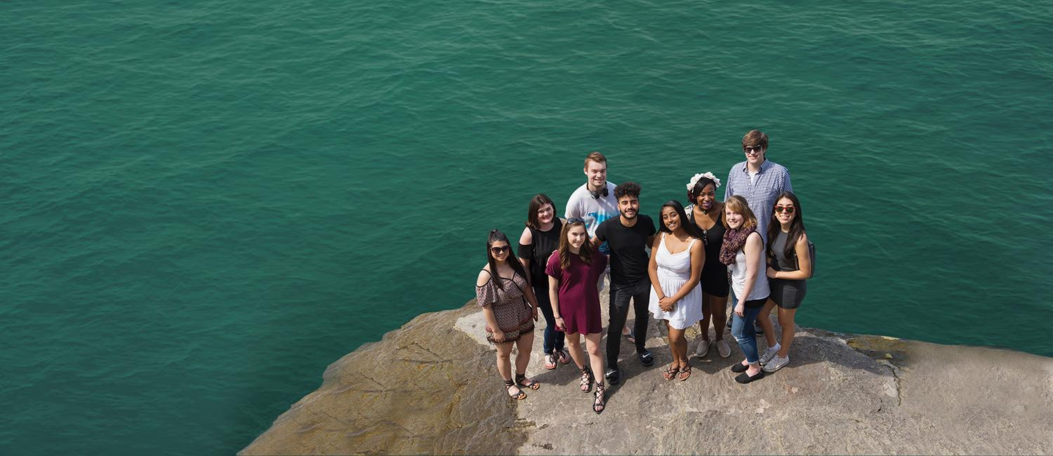 Students stand in a group next to Lake Ontario