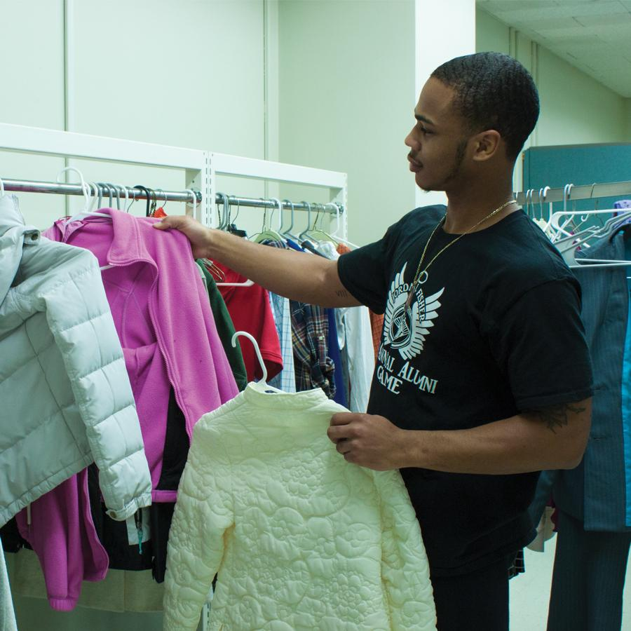 Student placing clothes on rack