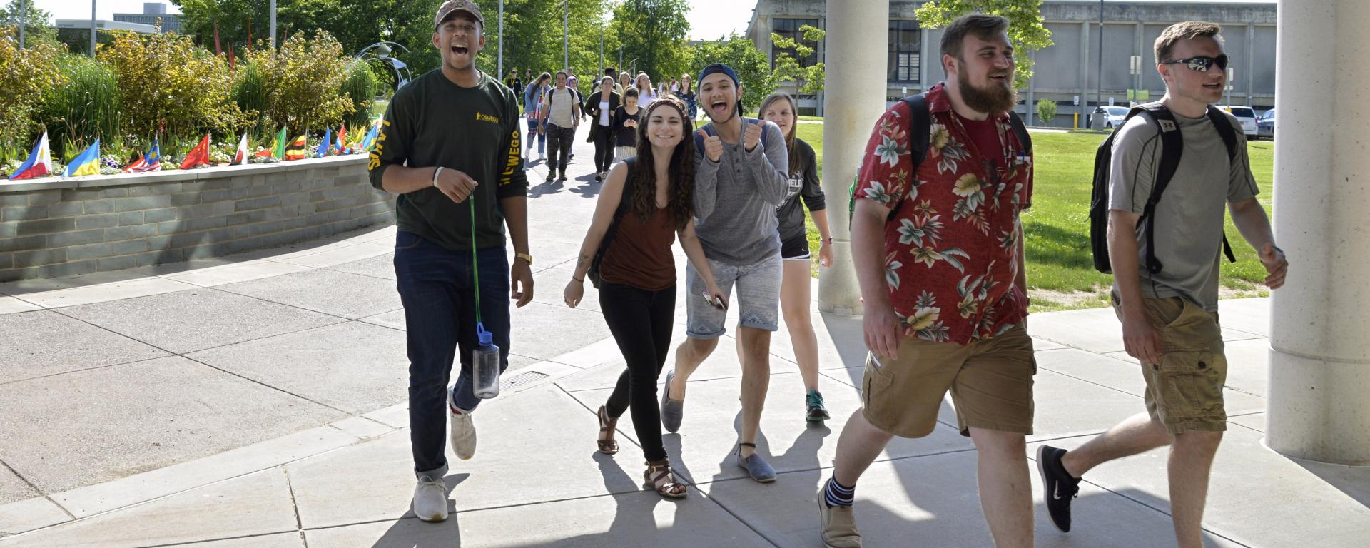 Laker Leaders walking into Marano Campus Center during Orientation. The Laker Leaders are looking towards the camera smiling. It is a bright and sunny day