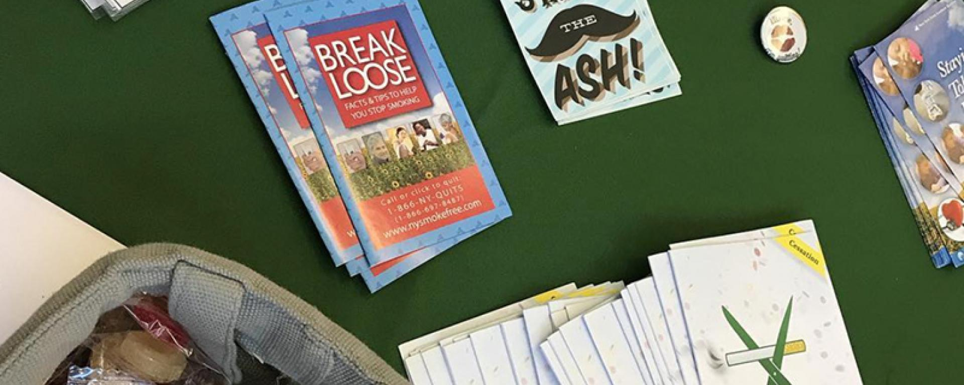 Table filled with pamphlets and stickers about kick butts day