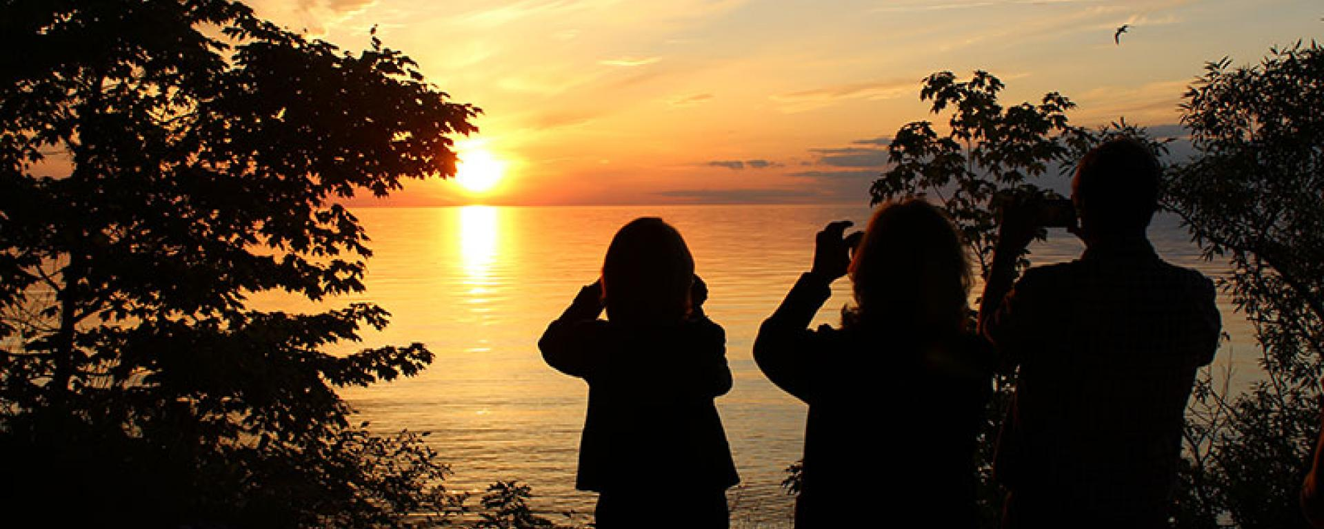 3 silhouettes of people taking photos of the Oswego sunset