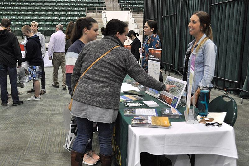 Students speaking with a vendor in career day