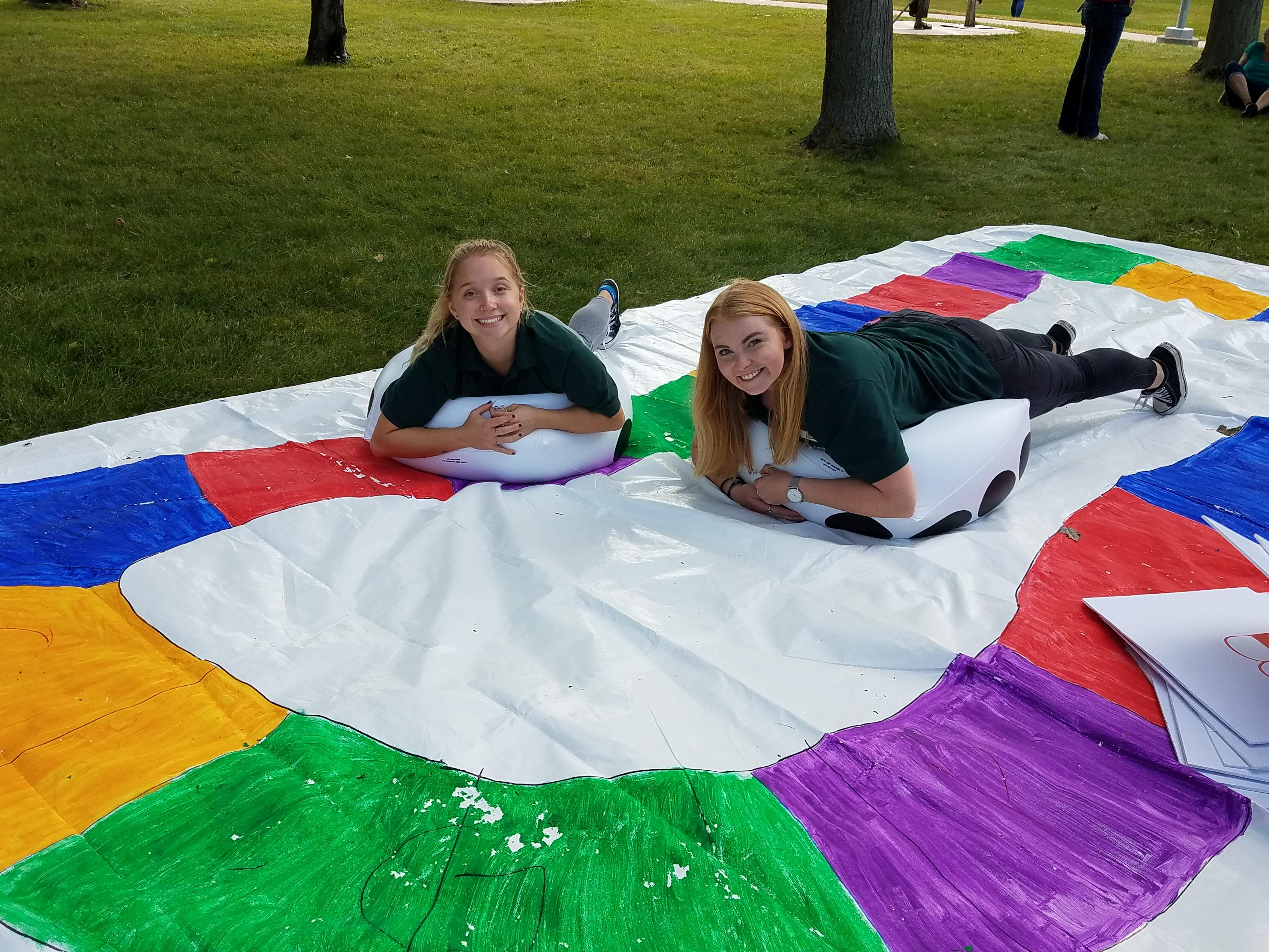 Two students on a giant game board with inflatables