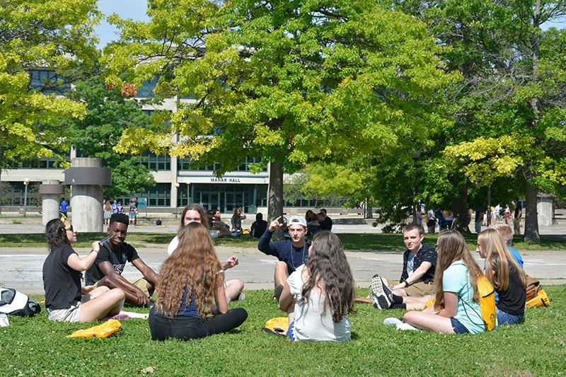 Group of students sitting in a circle on the grass