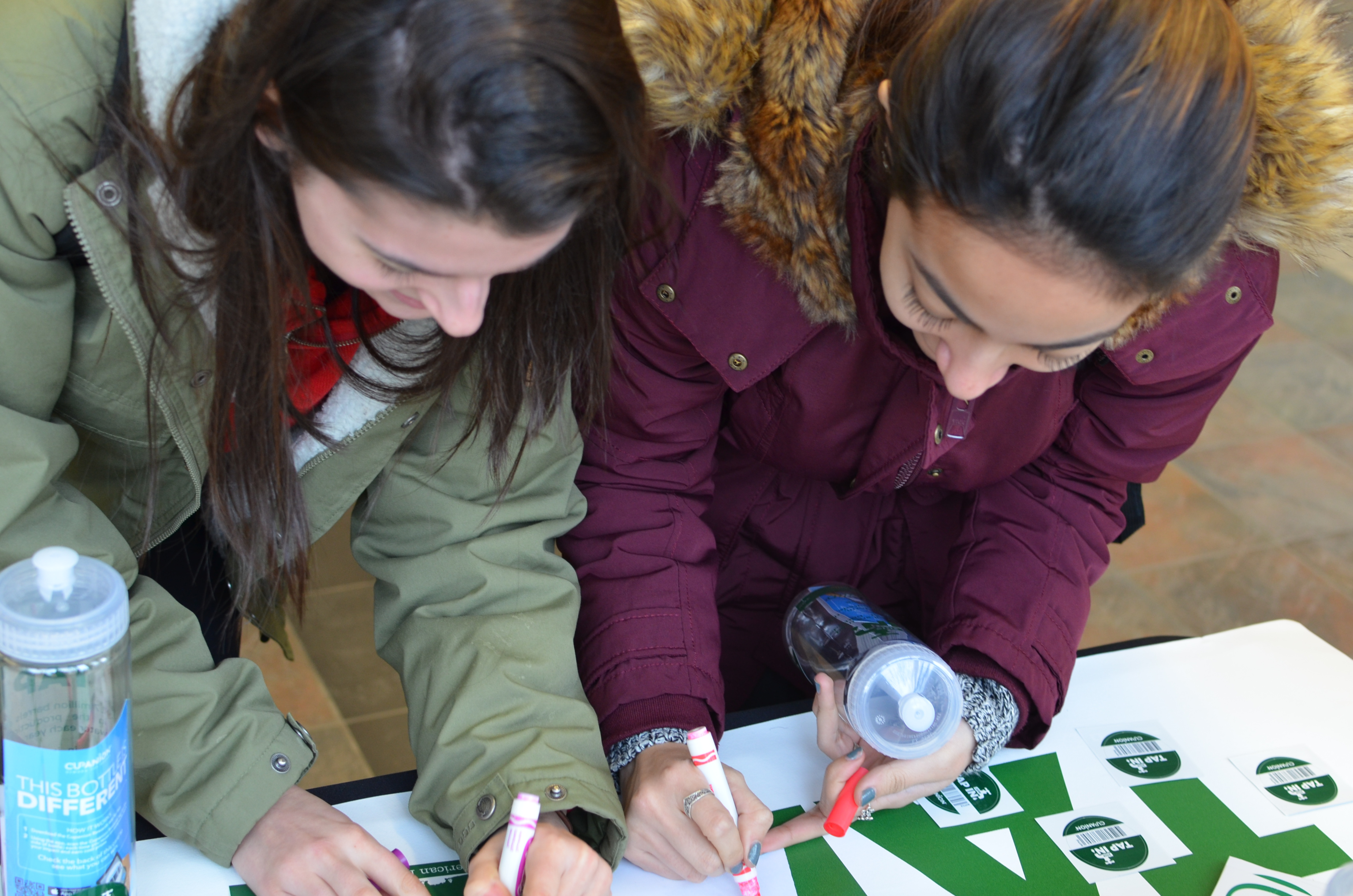 Two students sign the Tap In pledge to use only reusable bottles for the duration of the initiative.